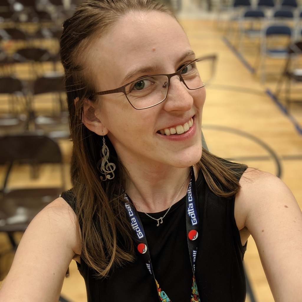 Woman smiling with glasses, musical earrings, and a Pokemon lanyard