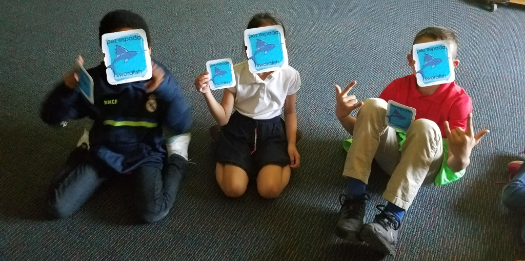 3 student holding up swordfish cards