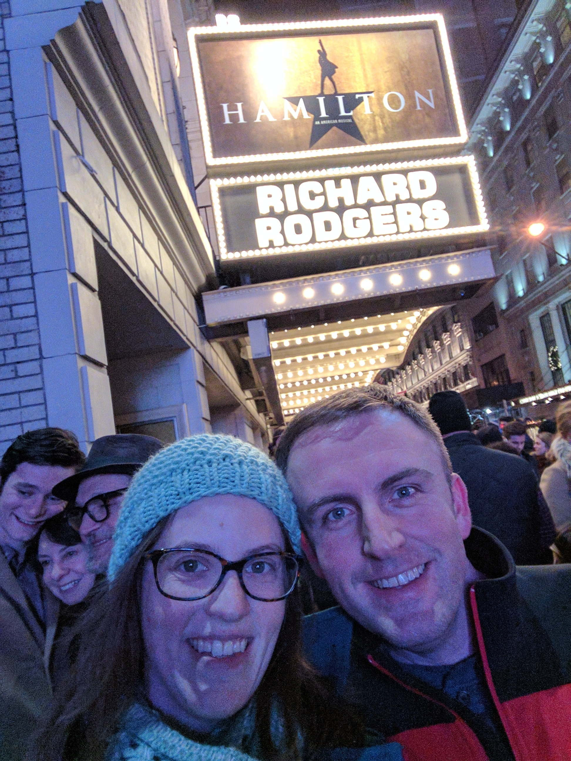 Lindsay and her husband at night, about 30 feet in front of the sign for Richard Rodgers and Hamilton the musical
