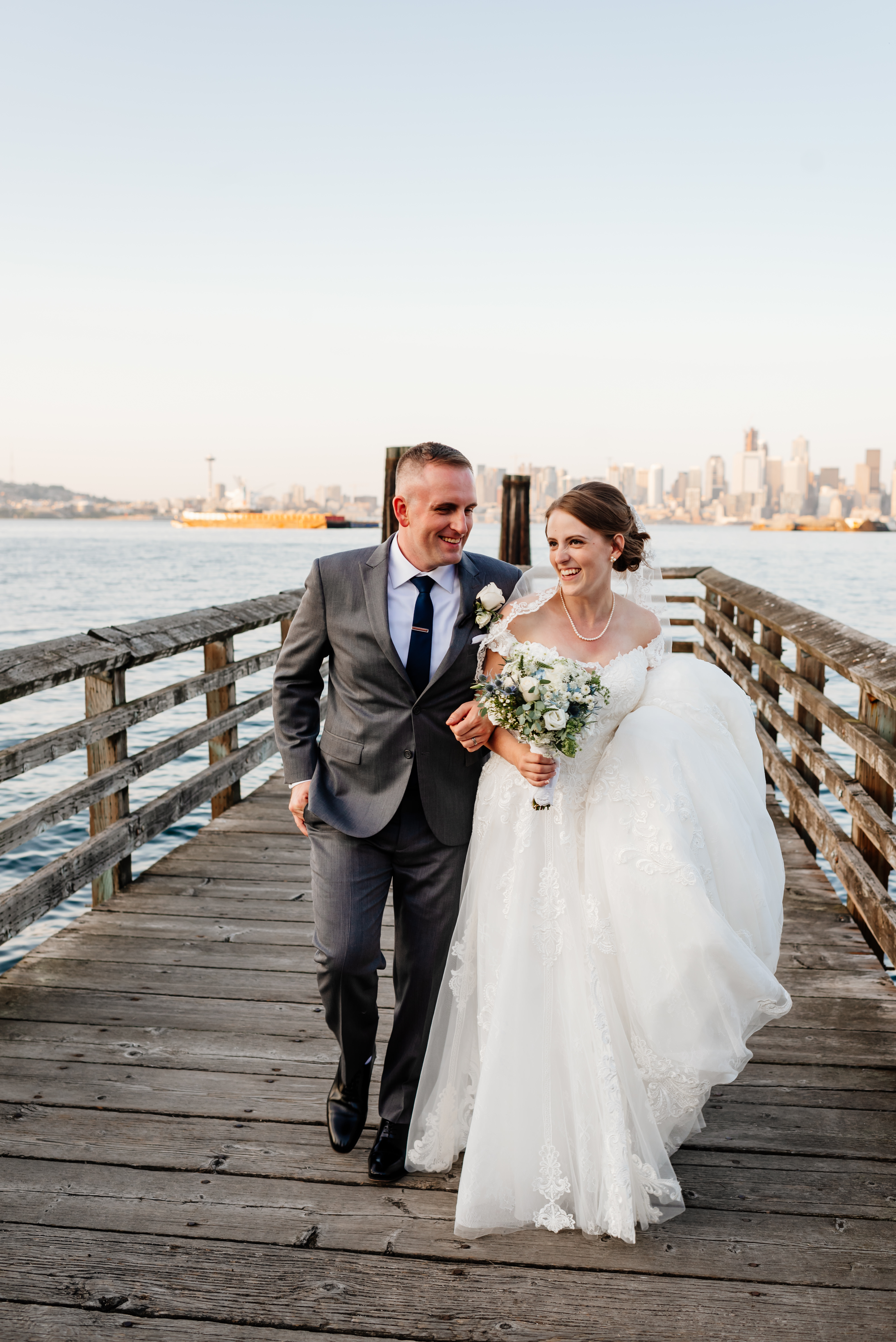 Lindsay in long white wedding dress holding bouquet, linked arms with husband in gray suit smiling on dock overlooking Seattle.